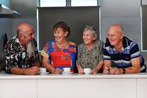 Four senior people having a drink together